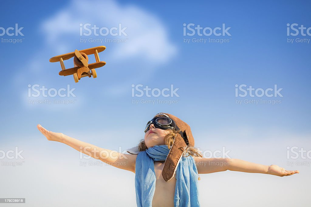 Kid playing with toy airplane under clear blue sky stock photo