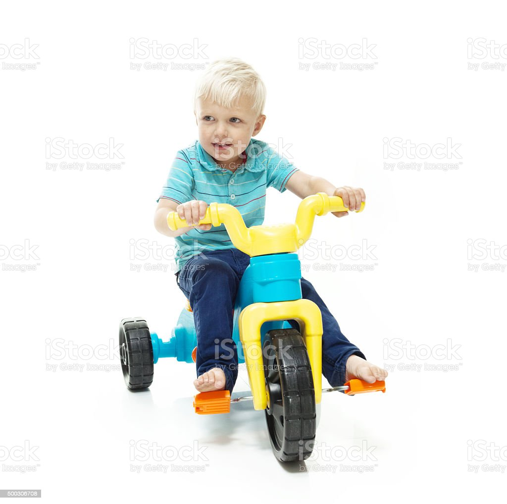 Kid riding tricycle stock photo