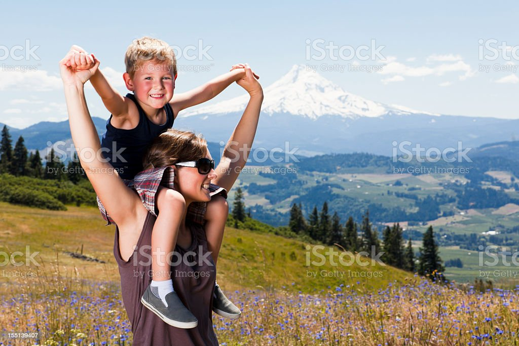 A kid sitting on his moms shoulders with a scenic mountain royalty-free stock photo
