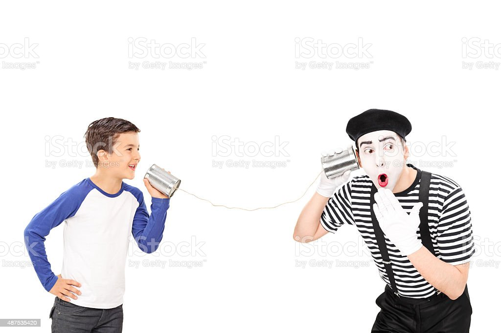 Kid talking to a comedian through a tin can phone stock photo
