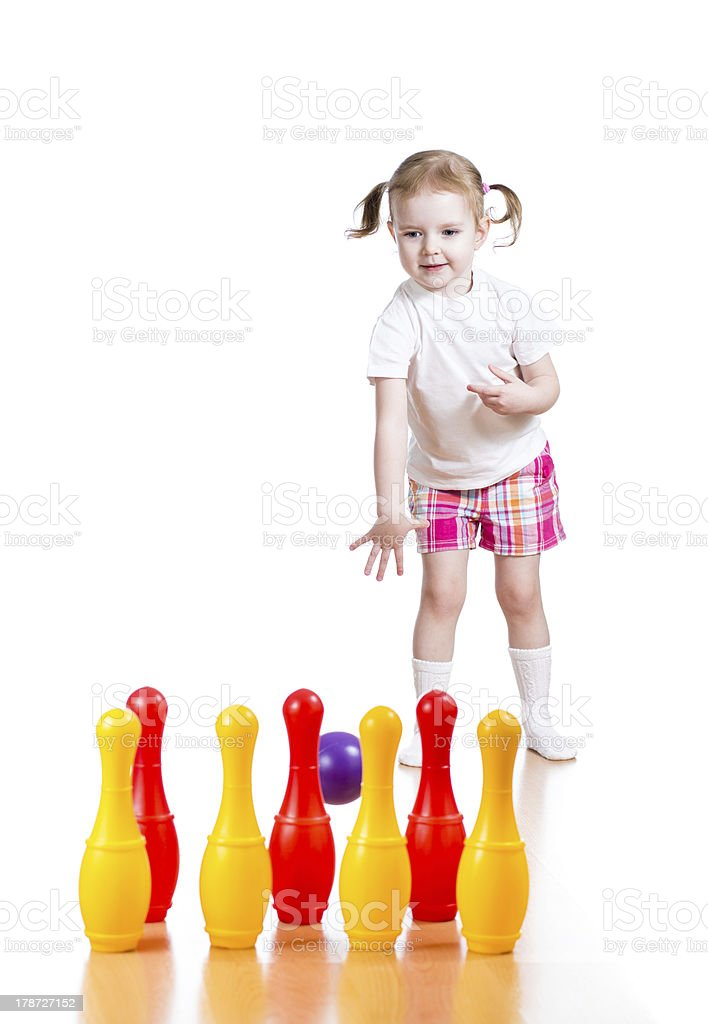 Kid throwing ball to bowling pins toy. Focus on girl. stock photo