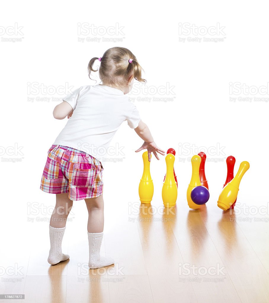 Kid throwing toy ball to bowling pins. Focus on child. stock photo