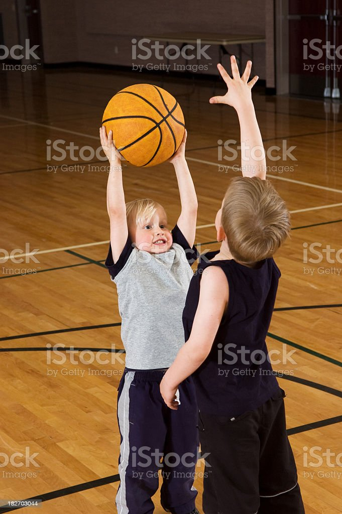 A kid trying to score against his friend royalty-free stock photo