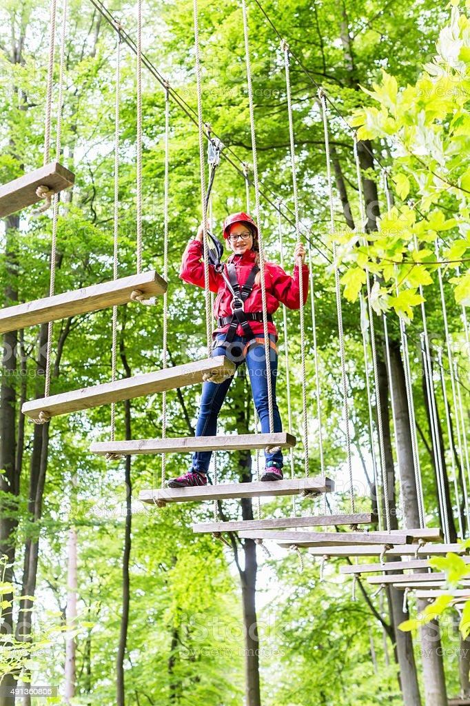 Kid walking on rope bridge in climbing course stock photo