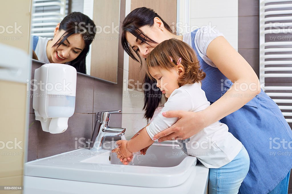 Kid washing hands with mom in the bathroom. stock photo