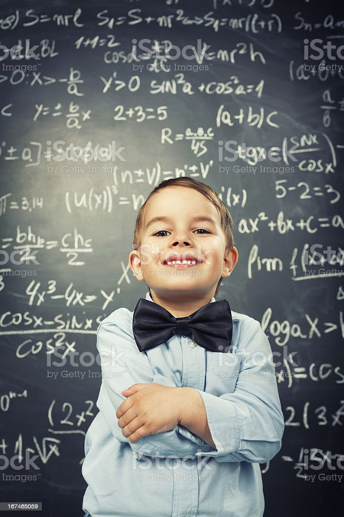 Kid wearing a bow tie and smiling in front of math equations royalty-free stock photo