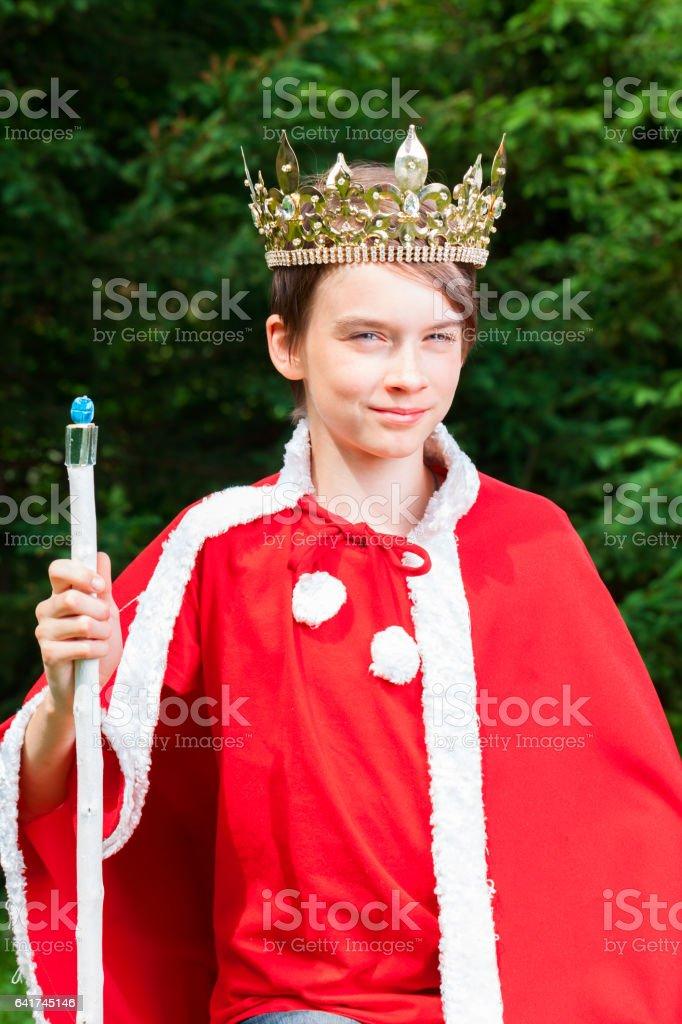 Kid wearing crown acting king stock photo