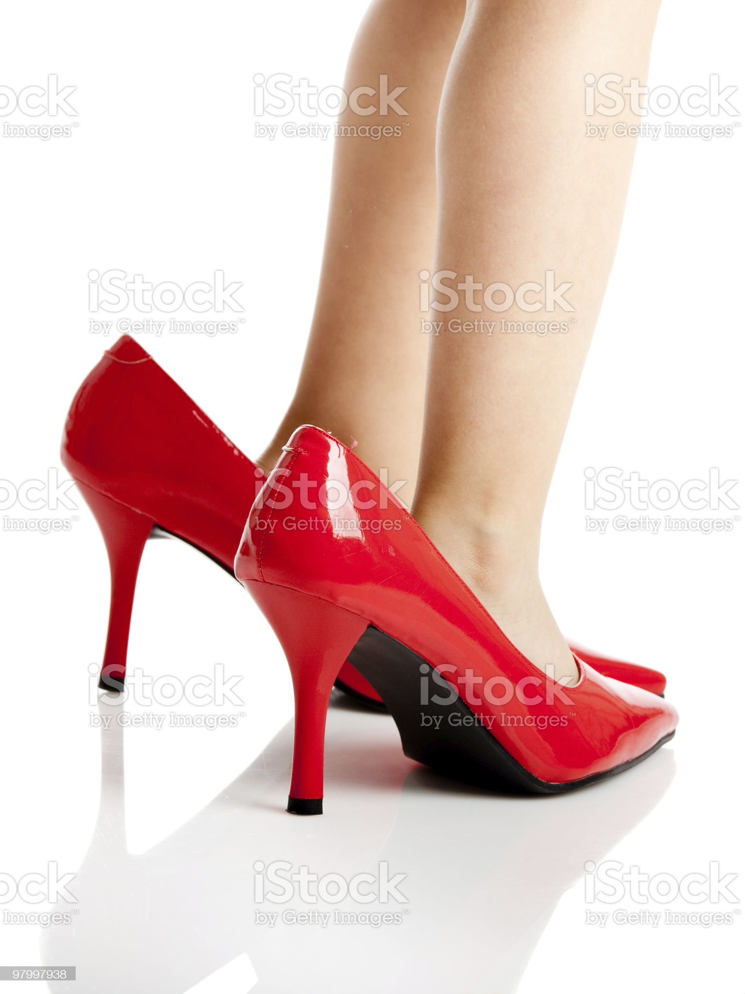 Kid wearing mother's red high heels pretending to be adult royalty-free stock photo