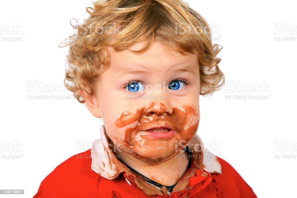 A kid with chocolate ice cream smeared all over his face stock photo