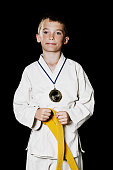 Kid with gold medal in his karate kimono
