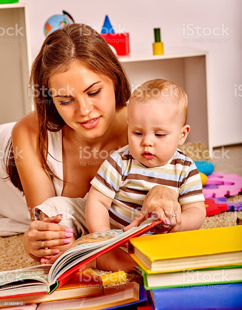 Kid with mother baby boy lying on floor and read stock photo