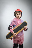 Kid with skateboard wrapped in plastic bubble by overprotecting parent