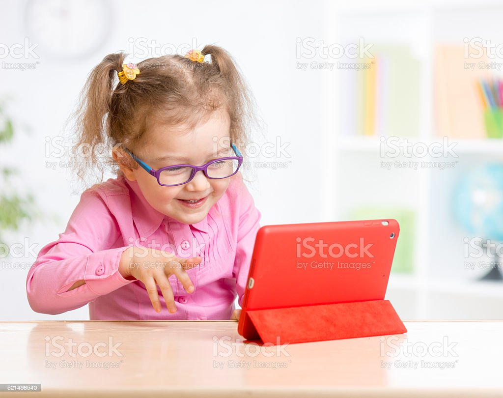 Kid with tablet PC in glasses learning stock photo