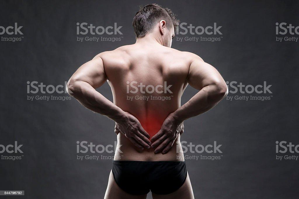Kidney pain. Man with backache. Handsome muscular bodybuilder posing stock photo