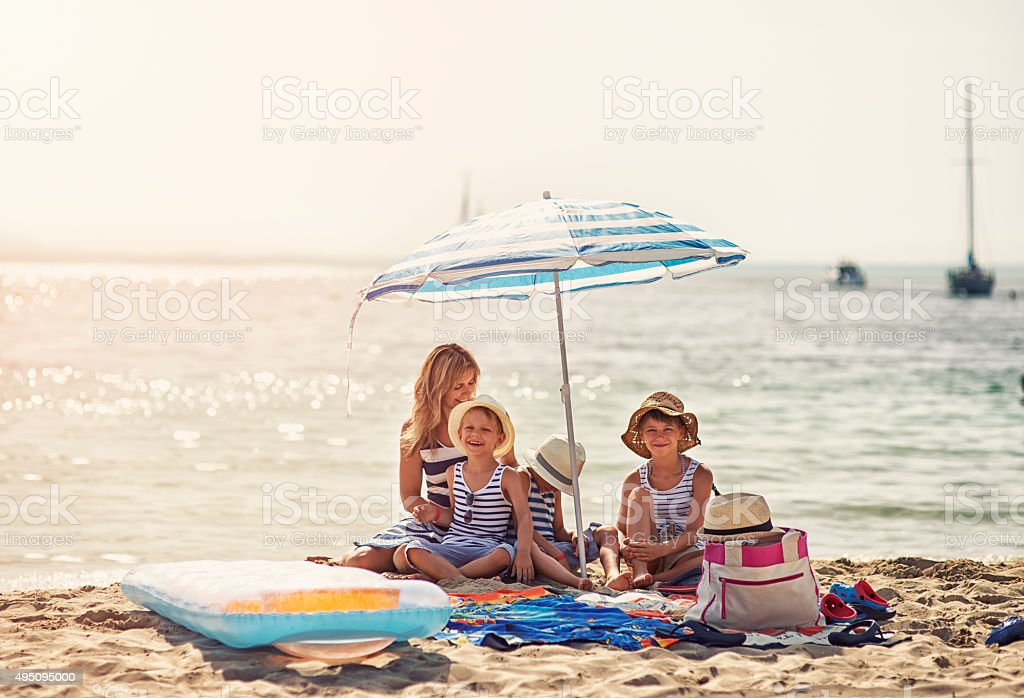 Kids and mother enjoying summer vacation on the beach stock photo