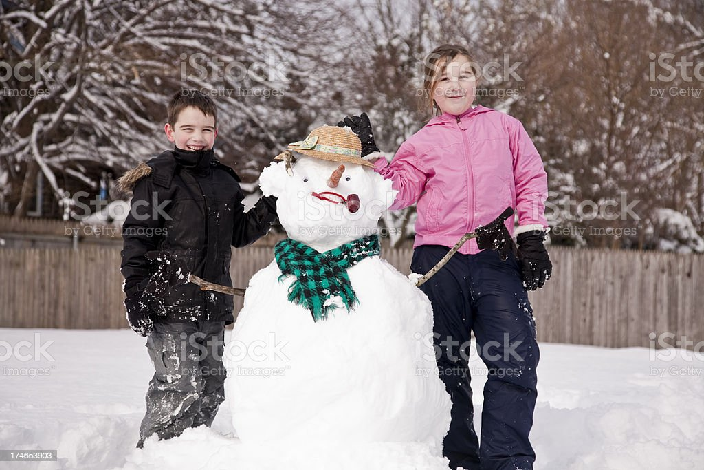 Kids and snowman stock photo
