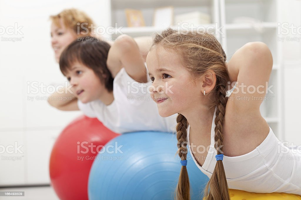 Kids and woman doing exercises with balls stock photo
