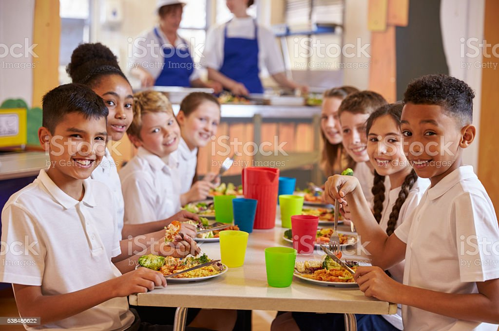 Kids at a table in a primary school cafeteria look stock photo