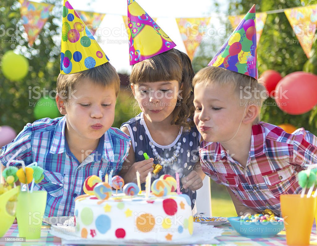 Kids at birthday party blowing candles on cake royalty-free stock photo