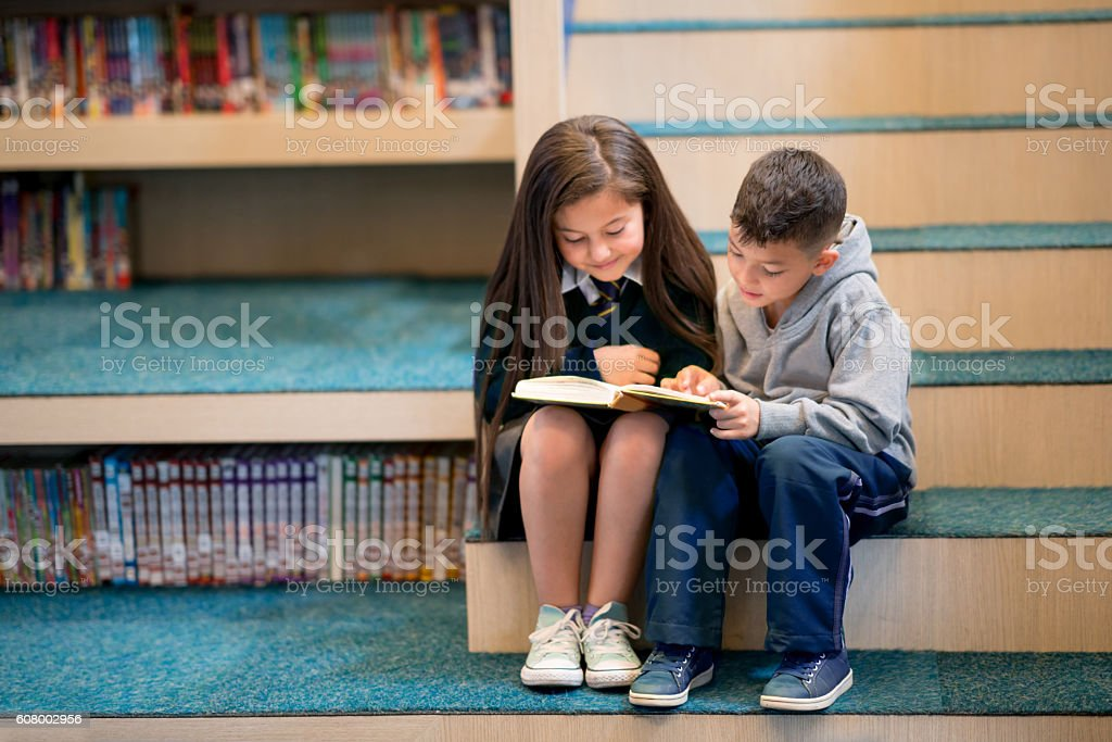 Kids at school reading a book stock photo