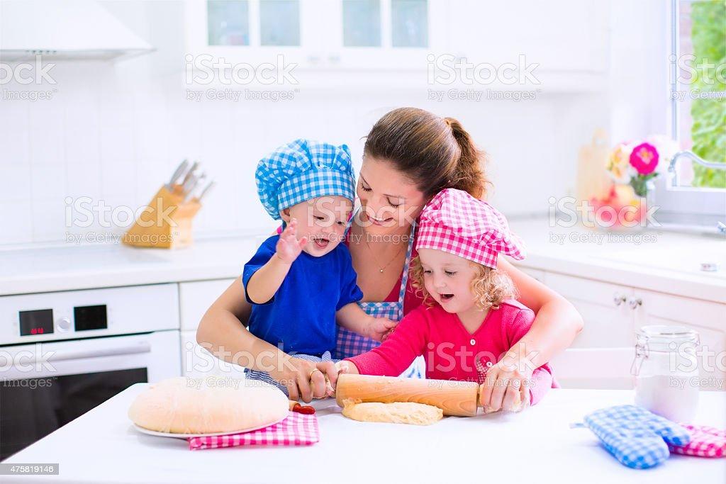 Kids baking in a white kitchen stock photo