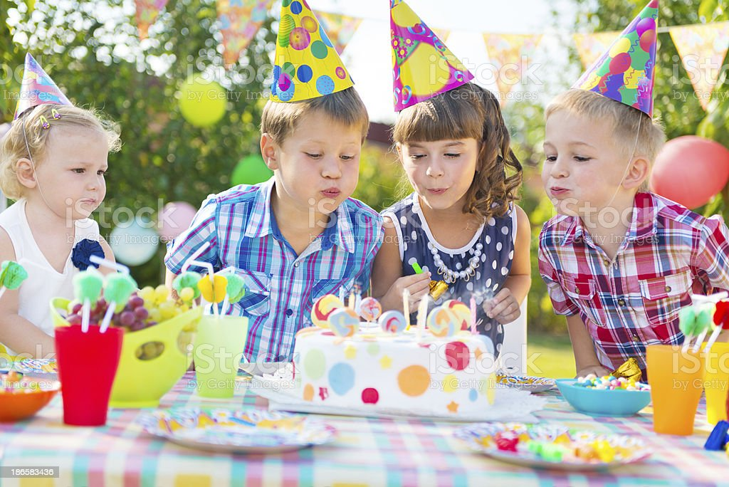 Kids blowing candles on cake at  birthday party stock photo