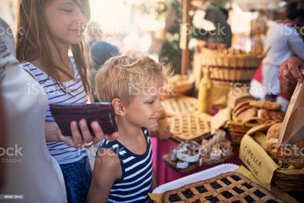 Kids boying cake at italian pastry street market stock photo