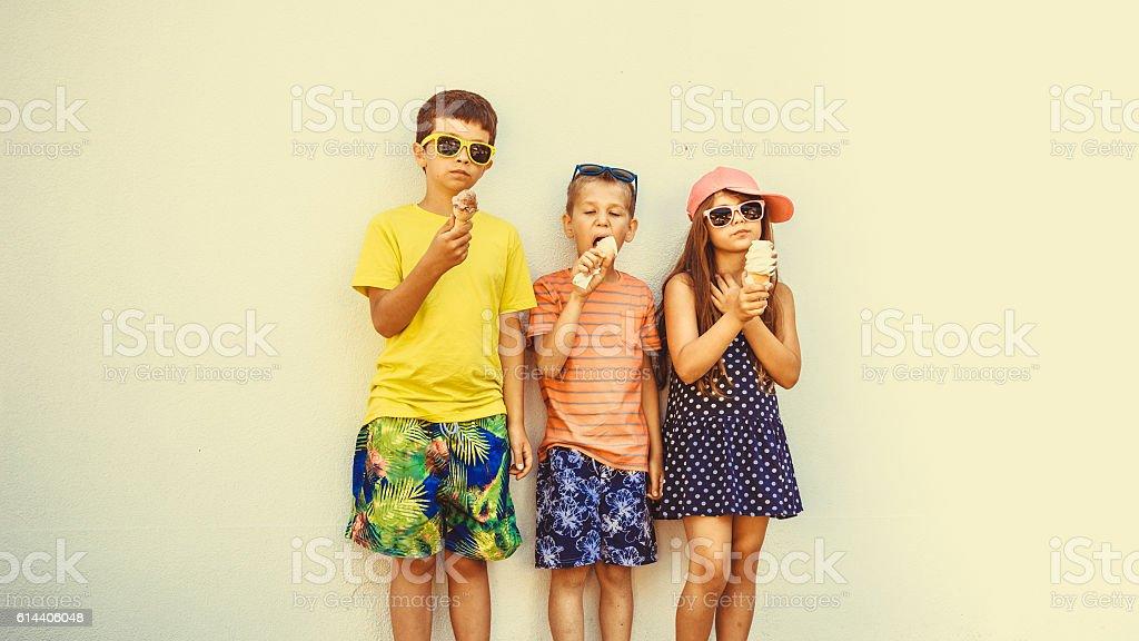 Kids boys and little girl eating ice cream. stock photo
