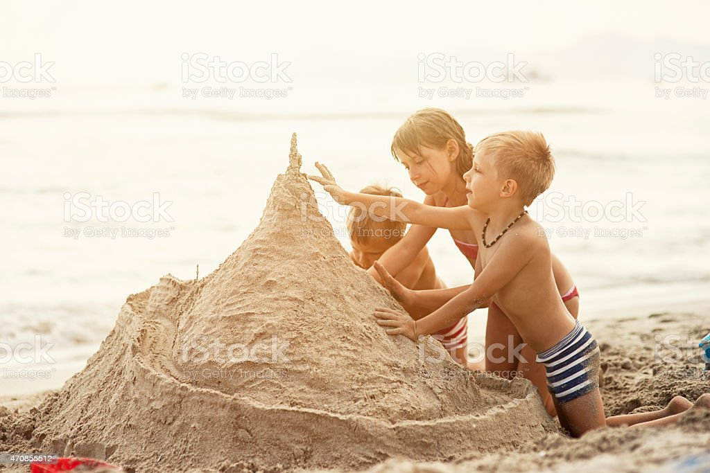Kids building a giant sandcastle stock photo