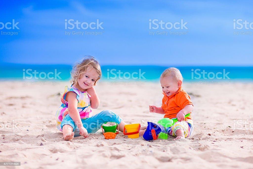 Kids building a sand castle on a beach stock photo