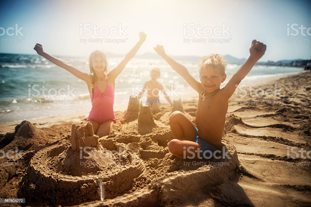 Kids building a sandcastle on a beautiful beach stock photo