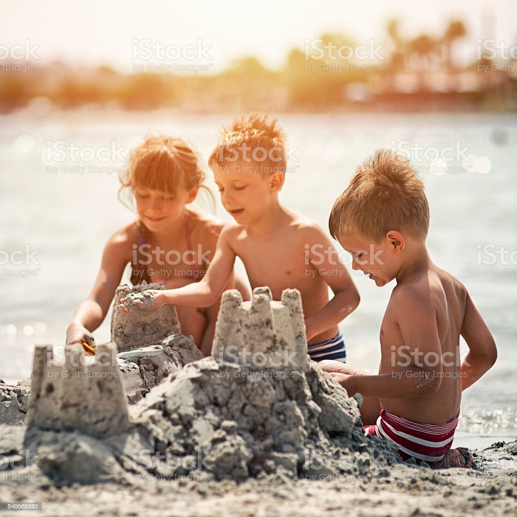 Kids building a sandcastle on beautiful beach stock photo