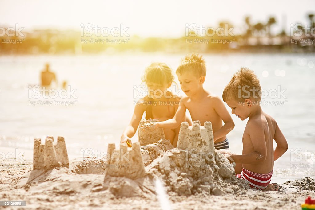 Kids building a sandcastle stock photo