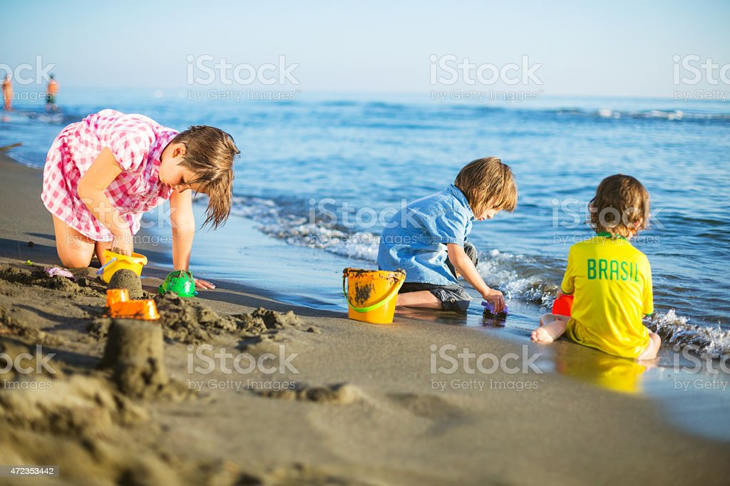 Kids building sandcastle stock photo