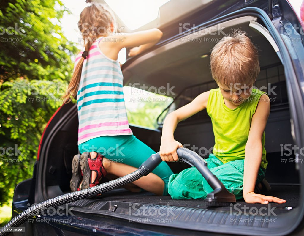 Kids cleaning family car interior stock photo
