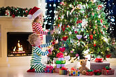Kids decorating Christmas tree in living room with fire place