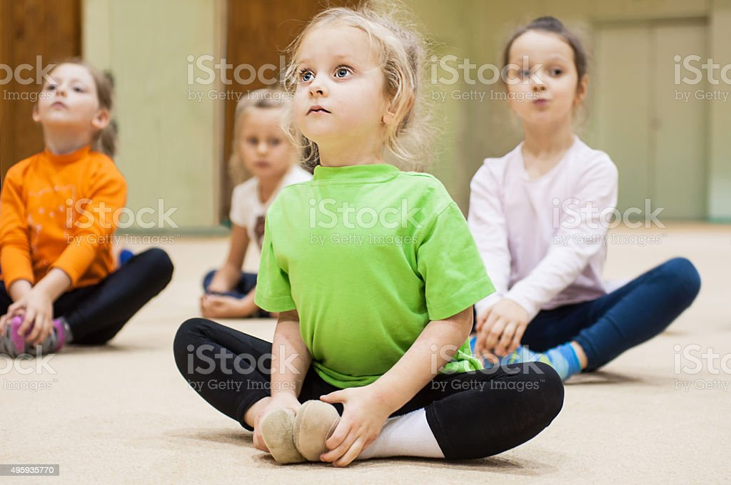 Kids doing exercise in gym stock photo