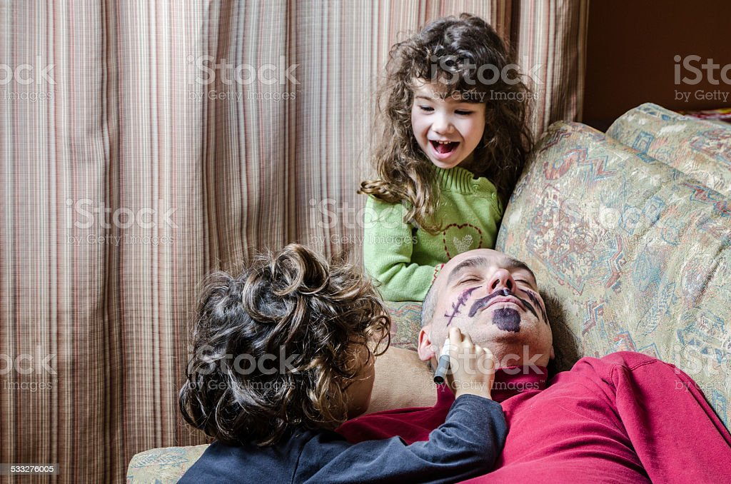 Kids drawing a mustache on father's face April fools day stock photo