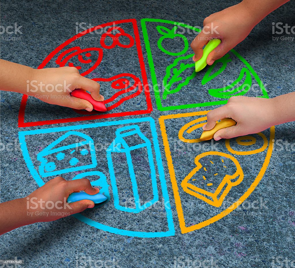 Kids drawing four food groups with chalk stock photo