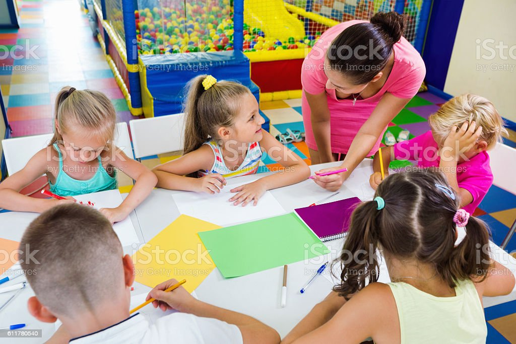 Kids drawing together with tutor at hobby group stock photo
