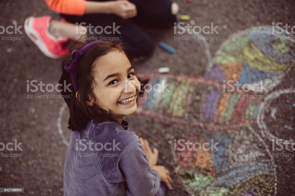 Kids drawing with chalk on asphalt stock photo