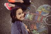 Kids drawing with chalk on asphalt
