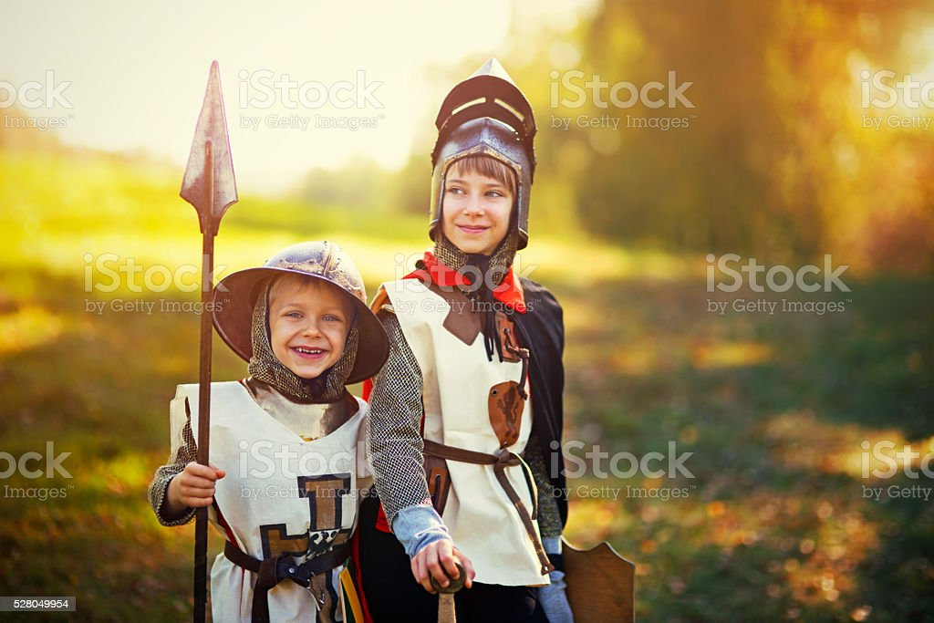 Kids dressed up as knights playing outdoors stock photo