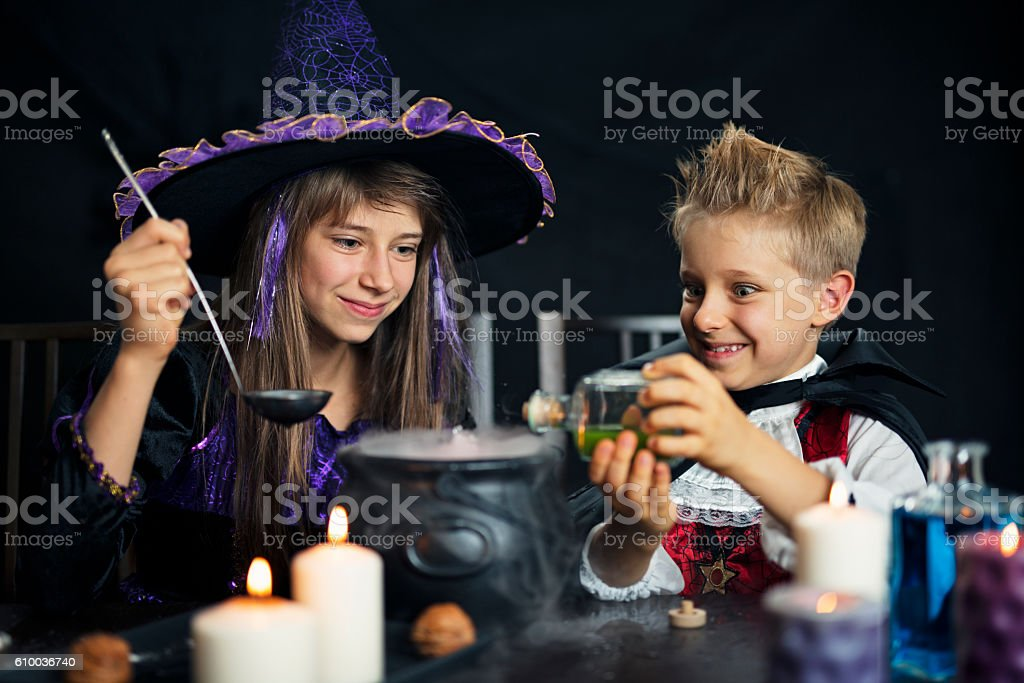 Kids dressed up as witch and vampire brewing potions stock photo
