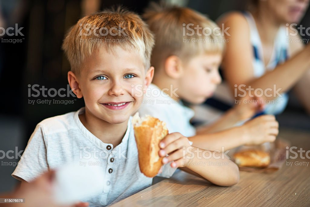 Kids eating baugette sandwiches at Paris cafe stock photo