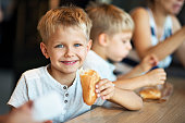 Kids eating baugette sandwiches at Paris cafe