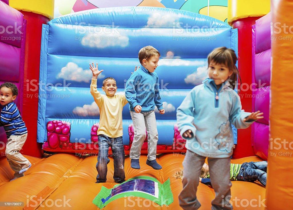 Kids enjoying in bouncy castle. stock photo
