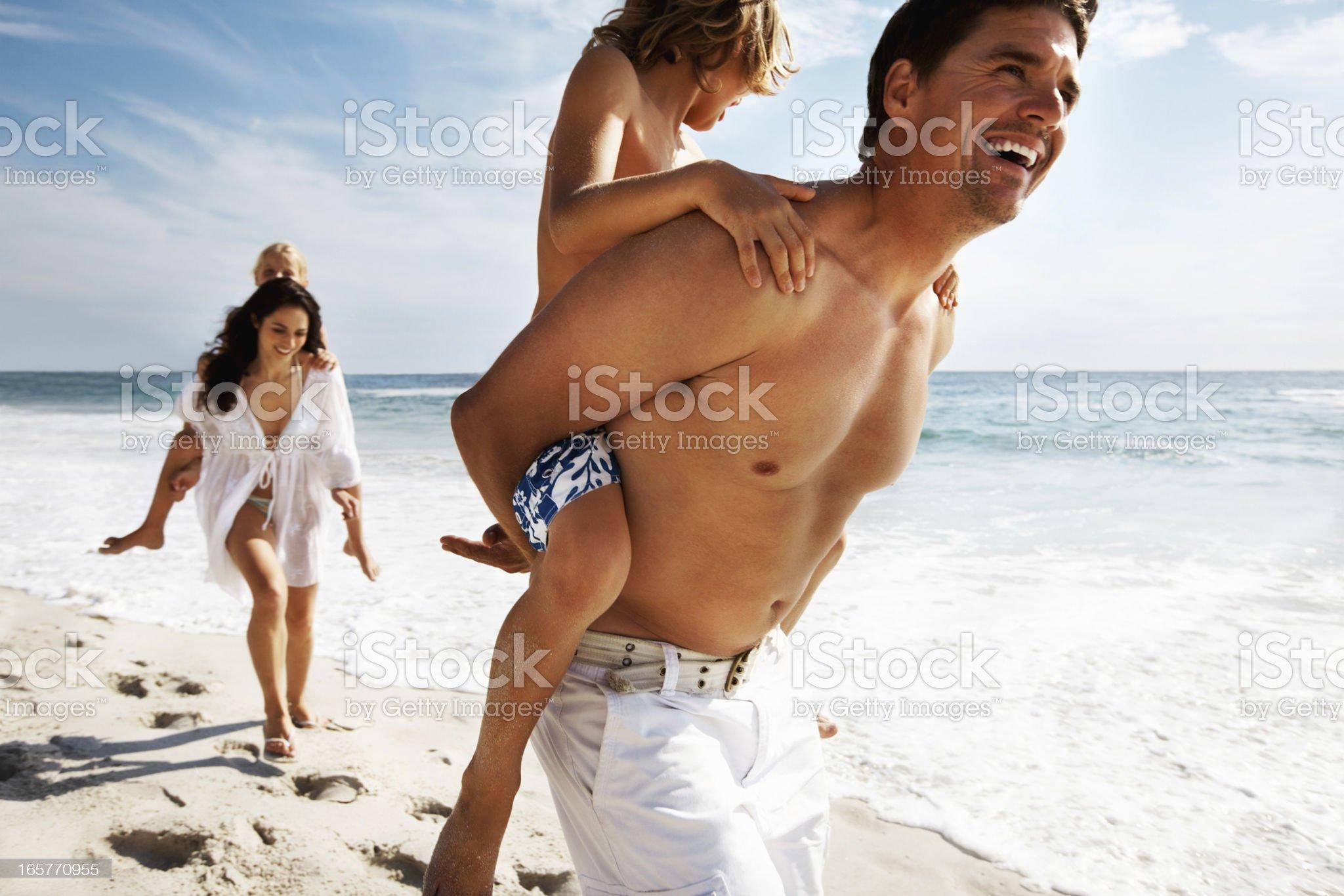 Kids enjoying piggy back rides on parents at the beach royalty-free stock photo