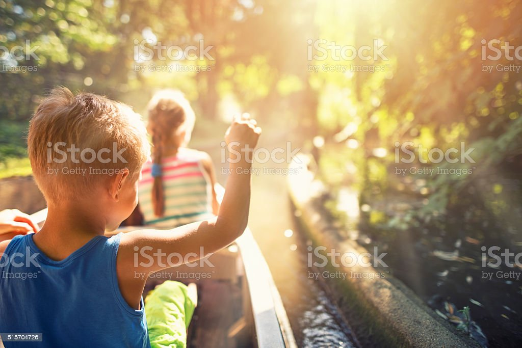 Kids enjoying ride in a boat through the forest river stock photo