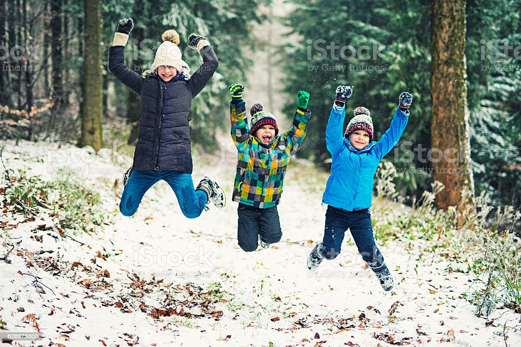 Kids enjoying the first snow in winter forest stock photo